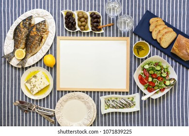 Freshly cooked seafood grilled sea bream fishes, sardines in olive oil and vegetable salad, olives, feta cheese, bread, water glasses served for two persons with frame copy space in the middle.