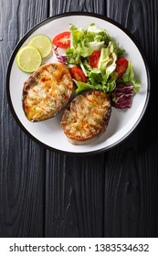 Freshly cooked sturgeon steaks served with fresh vegetable salad close-up on a plate on the table. Vertical top view from above