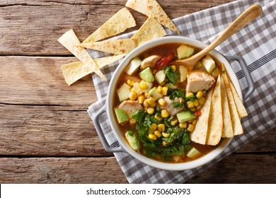 Freshly cooked tortilla soup with chicken and vegetables close-up on the table. Horizontal top view from above