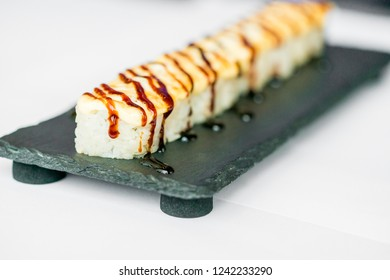 Freshly cooked uncut sushi roll on black board