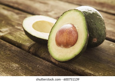 Freshly cut avocados on wooden table ready to make guacamole