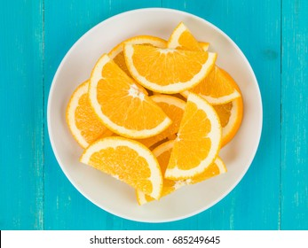Freshly Cut Juicy Orange Slices of Segments Against A Blue Wooden Background