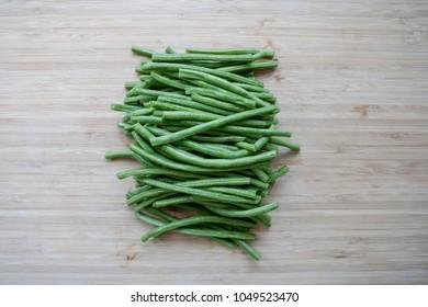 Freshly Cut Organic Green Beans on Wooden Cutting Board.