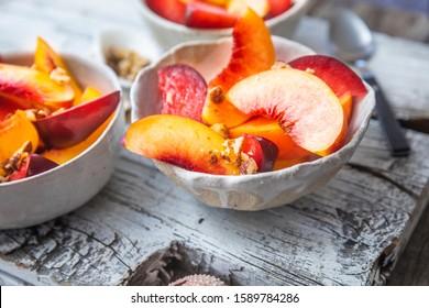 Freshly cut peaches in a white bowl
