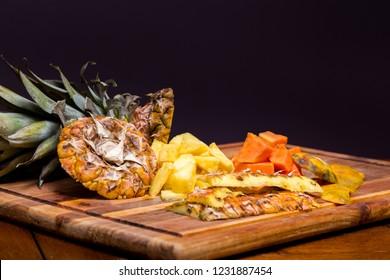 Freshly cut pineapple and papaya on a wood cutting board.