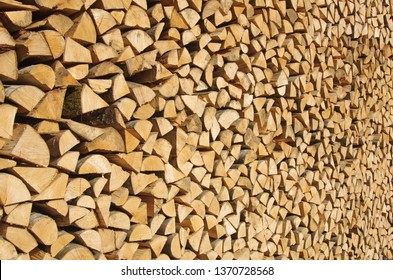 Freshly cut and stacked wood logs. Wooden abstract background. Renewable energy