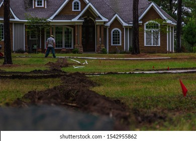 Freshly dug trenches for laying pipe to install a new irrigation system in a yard