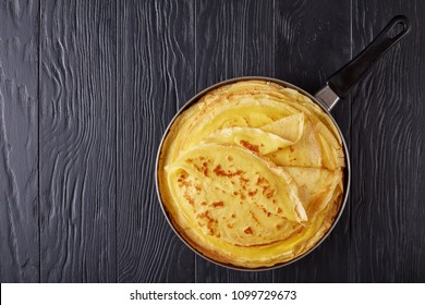freshly fried french crepes on a skillet on black wooden table, view from above