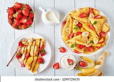 freshly fried homemade french crepes on a plate with strawberries, banana slices and fresh cream, horizontal view from above, close-up