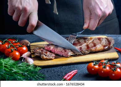 Freshly fried meat is cut into portions. Beef steak with blood.