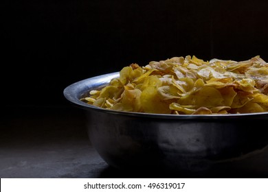 Freshly fried plantain chips in a bowl under soft, natural light.