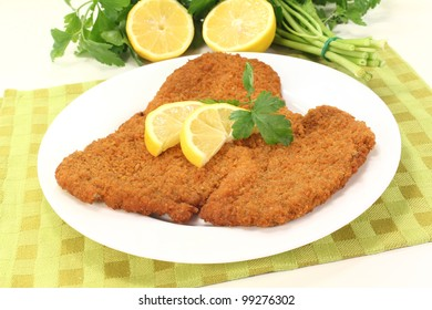 freshly fried Wiener Schnitzel with lemon slices and parsley on a napkin