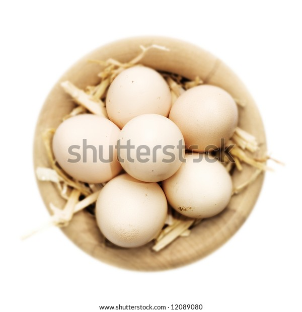 Freshly gathered eggs in a basket over white