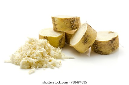 Freshly grated mash of horseradish root and sliced circles isolated on white background
