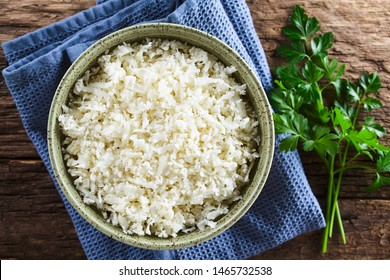 Freshly grated raw cauliflower rice in bowl with fresh parsley leaves on the side, photographed overhead (Selective Focus, Focus on the cauliflower rice)