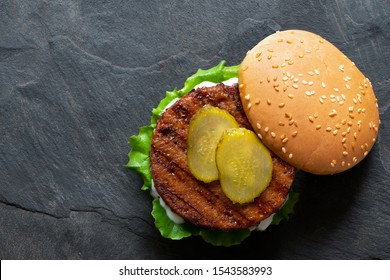 Freshly grilled plant based burger patty in bun with lettuce, slices of gherkin  and sauce isolated on black slate. Top view. Copy space.