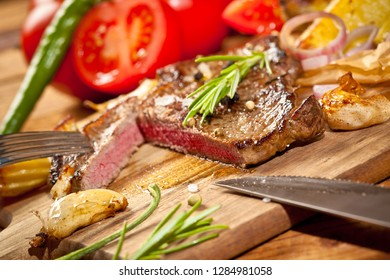 Freshly grilled steaks and vegetables on wooden cutting board