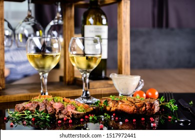 Freshly grilled T-bone steak served with cherry tomatoes thyme, rustic and a glass of white wine. ribeye steak, romantic dinner for two
