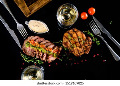 Freshly grilled T-bone steak served with cherry tomatoes thyme, rustic and a glass of white wine. Top View ribeye steak, romantic dinner for two