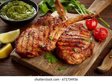 freshly grilled Tomahawk steaks on wooden cutting board