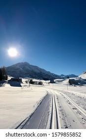 Freshly groomed cross Nordic ski track in pristine snow under a blue sky on a sunny winter's day in Andermatt, Switzerland.