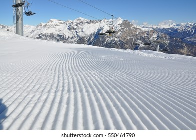 Freshly groomed ski piste with chairlift and mountainous background