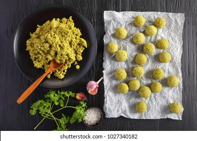 freshly ground chickpea mixed with greens and spices and raw falafel balls prepared to be fried or oven baked, classic middle eastern recipe, view from above
