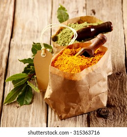 Freshly ground turmeric spice and matcha powder or green tea, in rustic brown paper packets with small wooden scoops and fresh tea leaves on a wooden table background