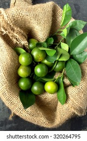 Freshly harvest Calamondin or calamansi lime on country classic gunny sack and wooden background.