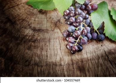 Freshly harvested Black grapes on wooden background with copyspace