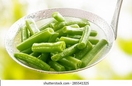 Freshly harvested diced steamed or boiled green runner beans in a kitchen ladle to be served as an accompaniment to a meal