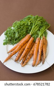 Freshly harvested raw carrots with green leaf tops and soil on skin over white plate