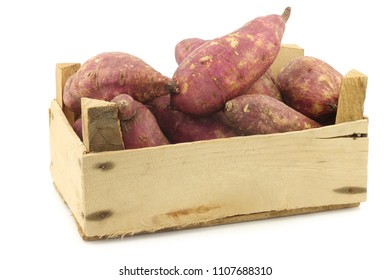 freshly harvested sweet potatoes in a wooden crate on a white background