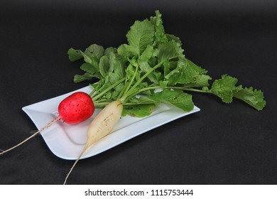 Freshly harvested white and red radishes with green leaves on a white plate against a black background