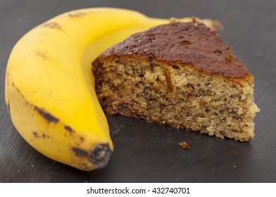 freshly made banana cake and overripe banana on black slate surface
