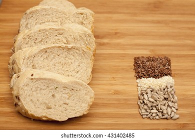 Freshly made bread with different seeds on wooden background