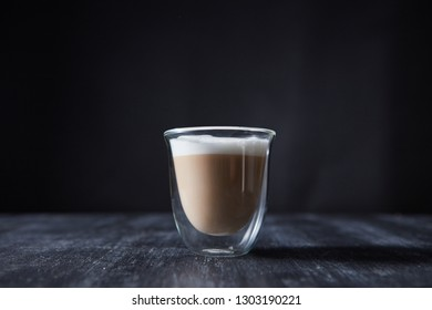Freshly made cappuccino with foam in a glass cup on a wooden table around a dark background with space for text.
