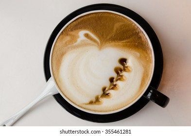 Freshly made cup of latte with leaf art. Coffee background. Toned image.