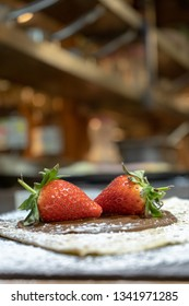 Freshly made delicious french crepe with strawberry and hazelnut spread on a table -vertical