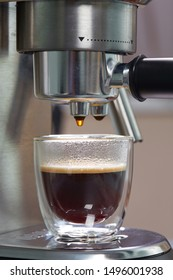 Freshly made espresso in a beautiful transparent double-circuit mug is on the coffee maker. Close up, vertical. Household coffee makers.