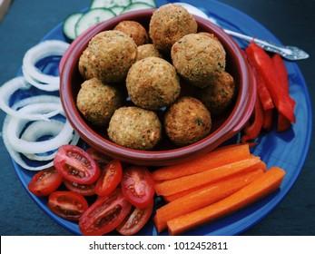 Freshly made falafel with sliced assorted raw vegetables. Halal food, middle eastern traditional cuisine. Black stone background. Vegetarian food, vegan snack. Side view.