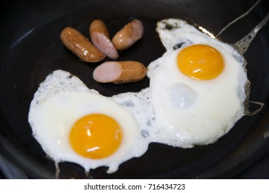 Freshly made fried eggs and sausages on a  pan