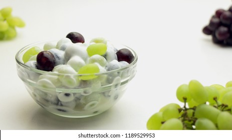 Freshly made grape salad with sour cream dressing in a glass bowl on a white background