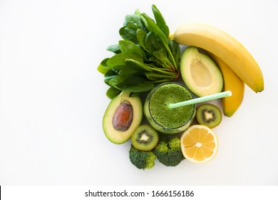 Freshly made green smoothie made of vegetables, fruits, herbs and greens. Glass of blended vegan beverage with ingredients around. Top view, close up, copy space, background.