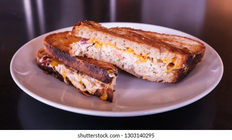 Freshly made grilled tuna melt sandwich with cheddar cheese and whole wheat bread.