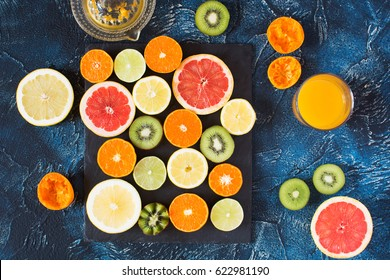Freshly made juice and fruits rich in vitamin C: oranges, lemons, kiwis, grapefruits and limes on the black slate on the dark blue background, top view
