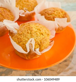 freshly made orange muffins on a plate