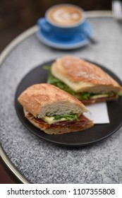Freshly made panini with prosciutto, cheese, greens and pesto