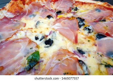 freshly made pizza with ham and olives
