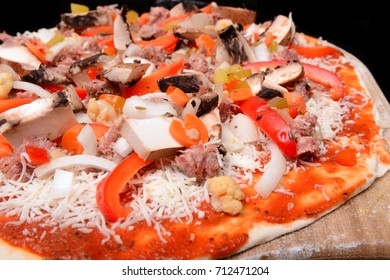 Freshly made pizza with onions, peppers, sausage, cheese and tomato sauce on a peal waiting to be baked